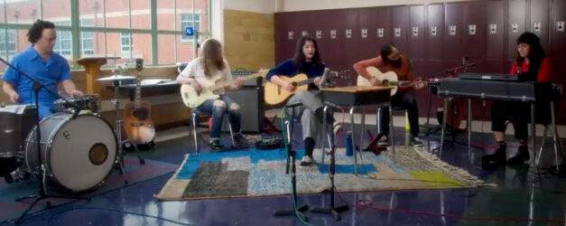 Lucy Dacus sits behind a Tinier desk